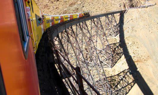 Orange and yellow train runs along railway bridge