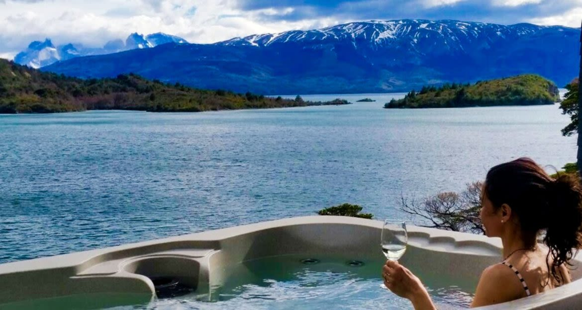 Woman sits in outdoor jacuzzi near mountains