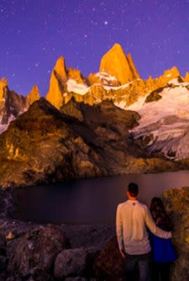 Couple stands near Patagonia lake at night