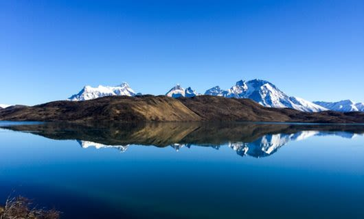 Reflection of Patagonia mountains in still lake