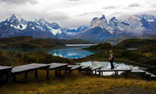Traveler stands on walkway near Patagonia lake