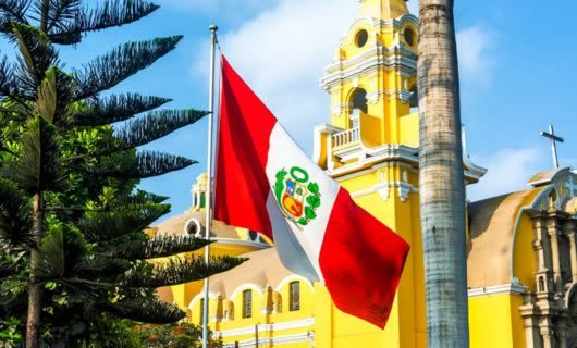 Peru flag in front of yellow building