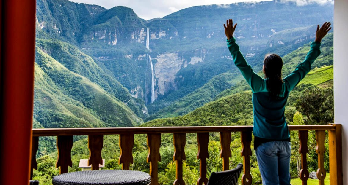 Traveler stands on balcony in Peru lodge