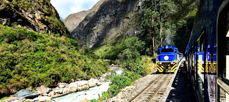 Trains travel through Peru mountain valley