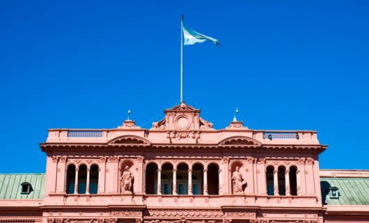 Blue flag on top of pink building