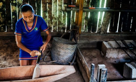 Woman in shed polishes a stick