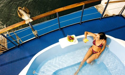 Woman lounges in pool on deck of cruise ship