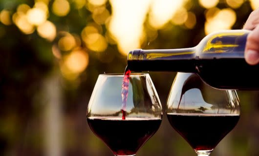 Red wine is poured into two glasses