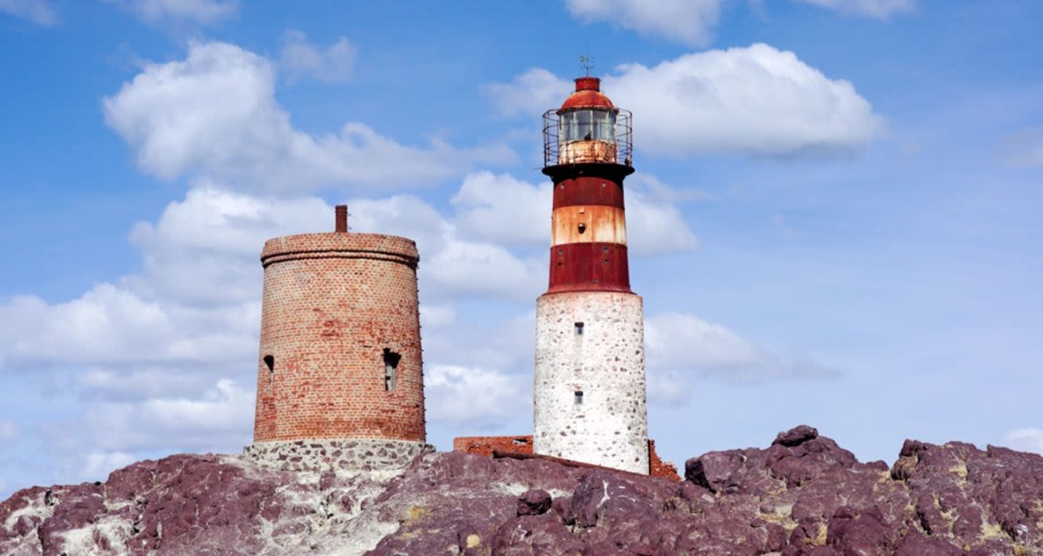 Red and white striped lighthouse on red rocks