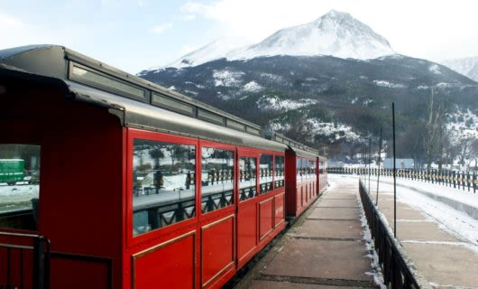 Red train sits on railway in front of mountain