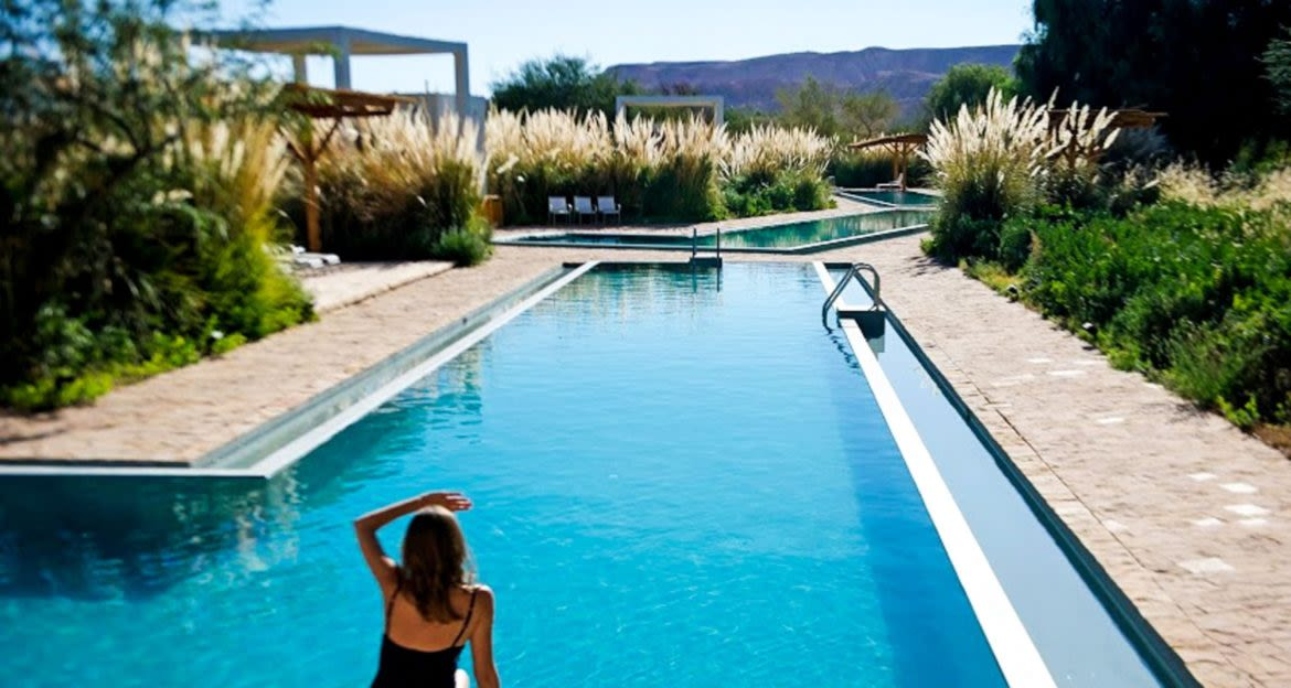 Woman looks at mountains from Atacama resort pool
