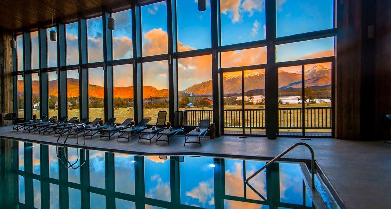 Indoor pool with wall of windows in Rio Serrada Lodge