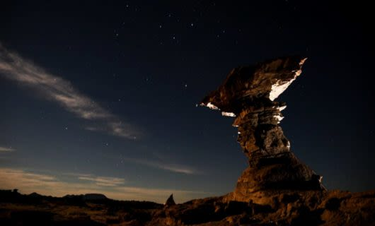 Rock structure stands in front of nighttime desert sky