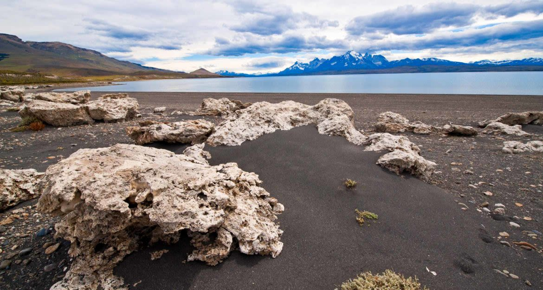 Large rocks on beach of lake near mountains