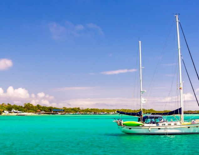 Sailboat sits on teal waters of the Galapagos