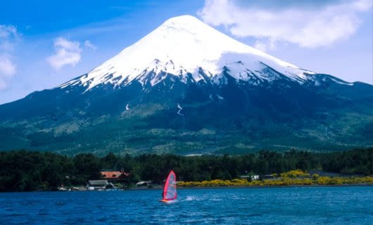 Red sailboat on water in front of mountain