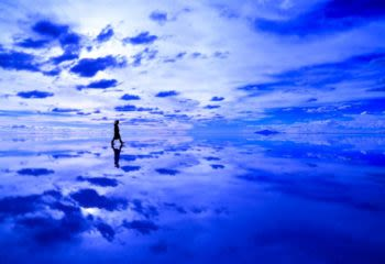 Person walking across reflective salt flats