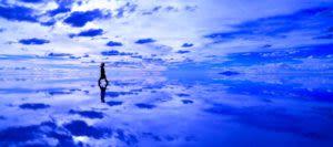 Person walking across reflective salt flats on a Bolivia tour