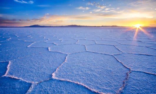 Low angle sun breaks over salt flats of Bolivia