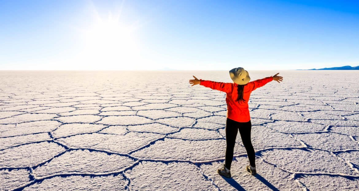 Woman stands on salt flats with arms spread