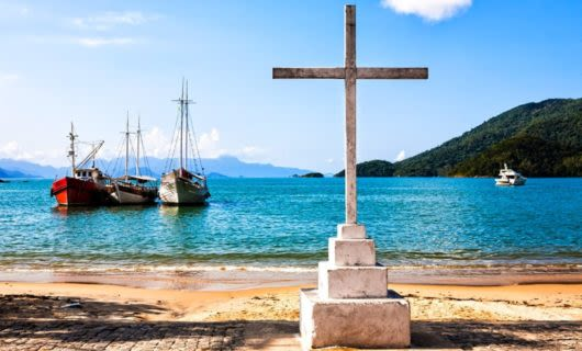 Cross stands on shore with boats in background