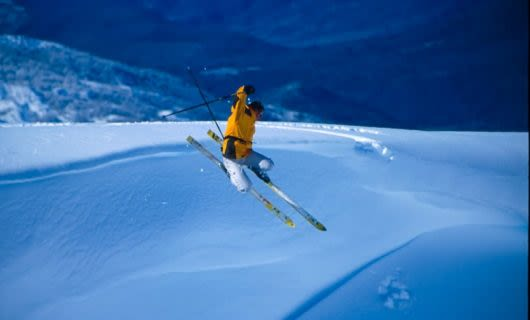 Skier wearing yellow jacket on ski jump