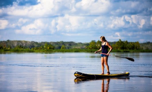 Traveler does stand-up paddleboarding on Amazon river