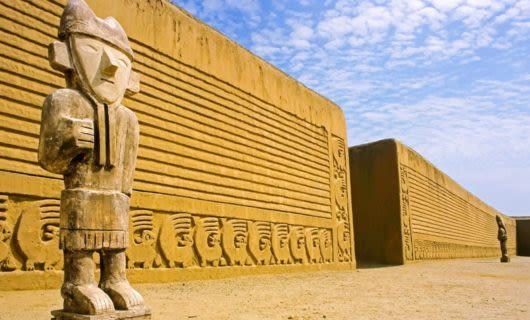 Statue near large stone wall