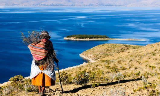 Woman gathers sticks near coastline
