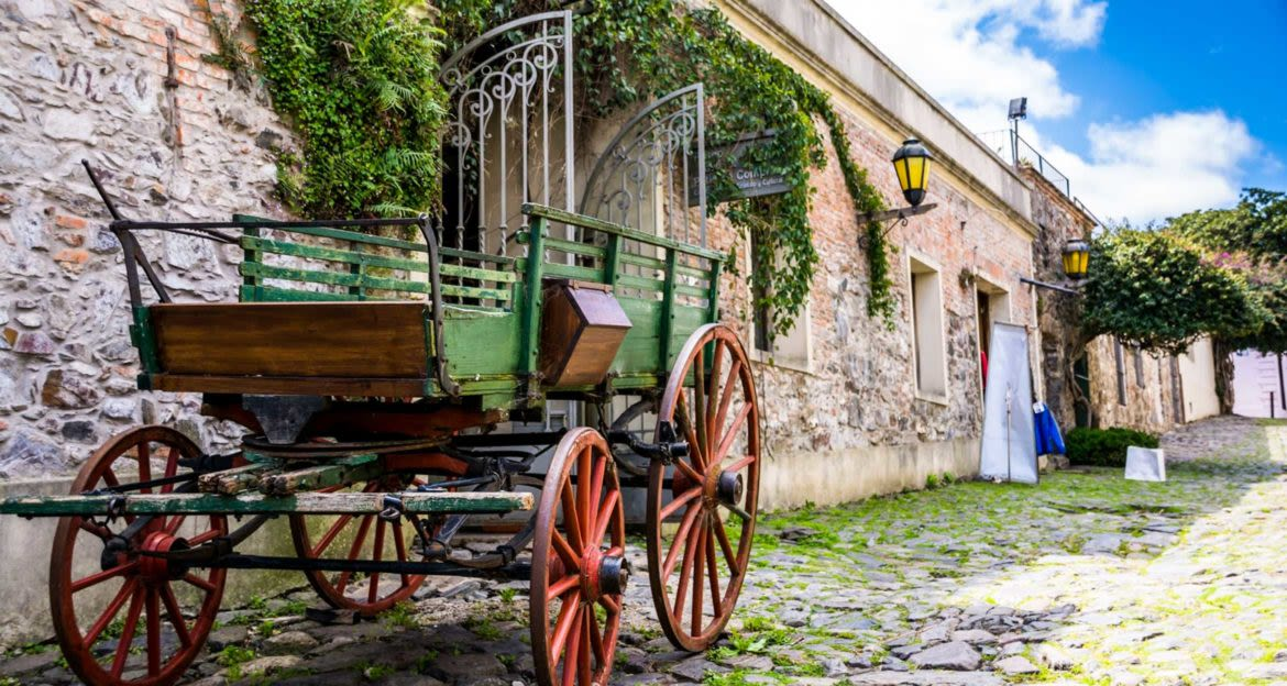 Wagon parked against stone wall on cobblestone road