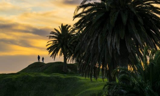 Two people stand on hill in Uruguay at sunset