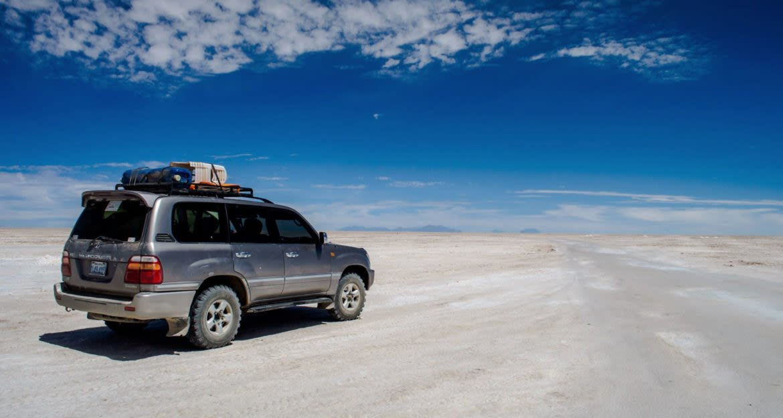 SUV drives across salt flats of Bolivia