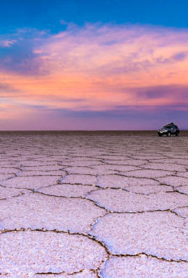 SUV drives across salt flats at sunset
