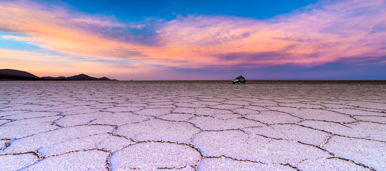 SUV drives across salt flats at sunset