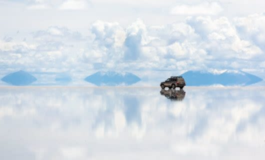 SUV sits on salt flats that reflect white cloudy sky