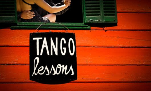 Tango lessons sign hands on red building