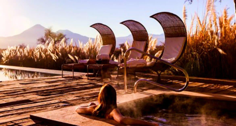 Woman sits in jacuzzi on deck of Tierra Atacama Hotel
