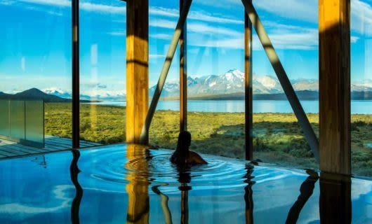 Woman floats in hotel pool near glass windows