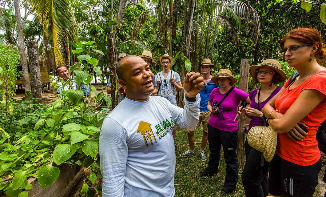 Tour guide speask to group in jungle