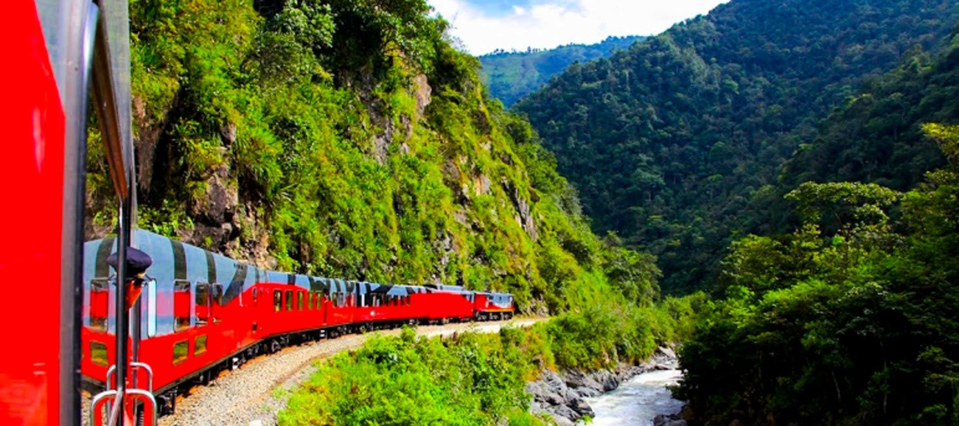 Red train travels through mountain valley