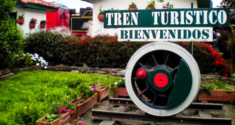 """""""Tren Turistico Bienvidos"""" sign above train wheel"""