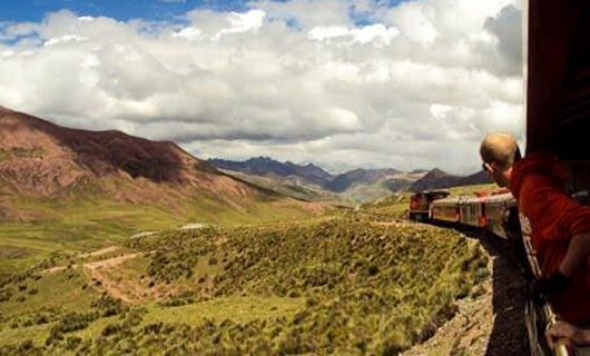 Man leans out window of South America train