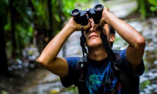 Traveler looks upward with binoculars