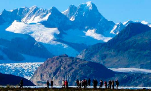 Travelers stand near Ainsworth Bay in South America