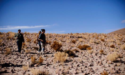 Travelers walk across rocky Atacama Desert