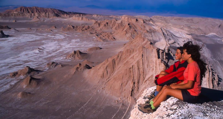 Travelers sit on edge of desert cliff