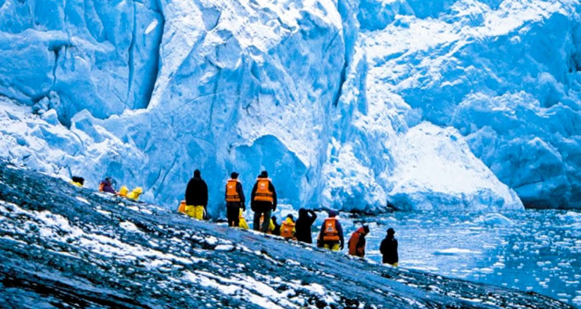 Travelers stand on rock and look up at glacier wall