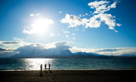 Travelers stand on beach of Patagonia lake