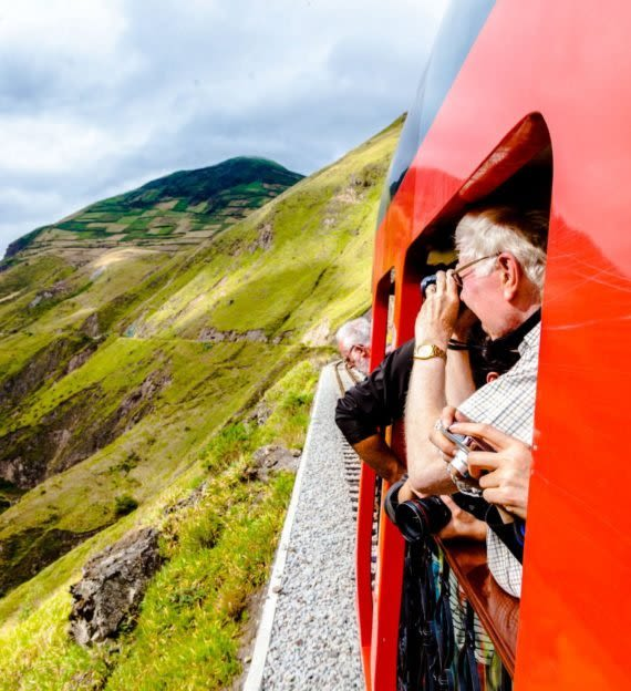 Travelers look out train window with binoculars and cameras