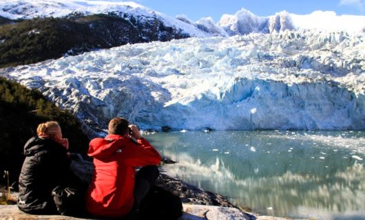 Two travelers sit to look at glacier